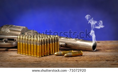 Smoking gun and bullets on old vintage wood table with copy space - stock photo