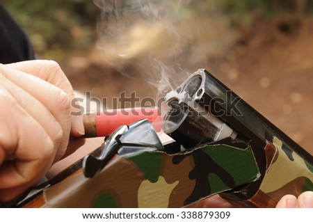 Smoking gun concept,  a double barrelled over/under shotgun immediately after firing with shallow depth of field focused on the smoke leaving the breech - stock photo