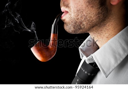 smoking his pipe in his hand - stock photo