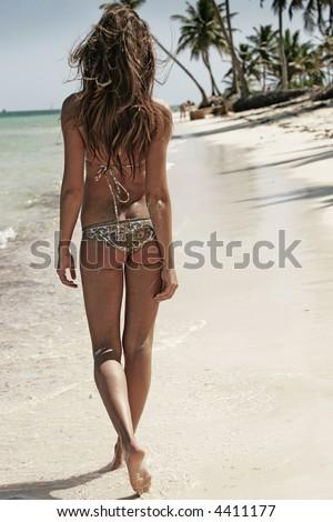 smoking hot brunette bikini model walking on the beach - stock photo