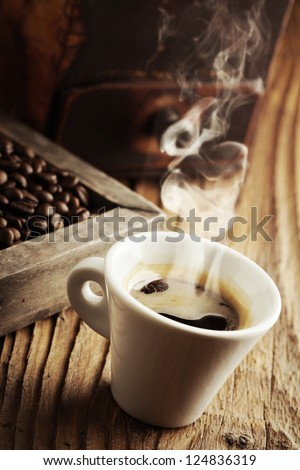 Smoking hot coffee with coffee beans - stock photo