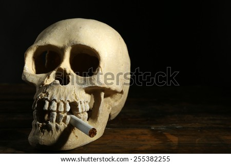 Smoking human scull with cigarette in his mouth on dark background - stock photo