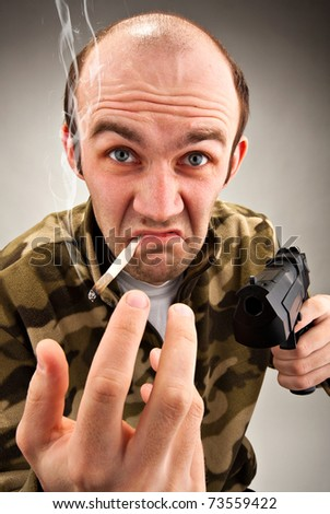 Smoking impudent bandit with gun attracting to himself - stock photo
