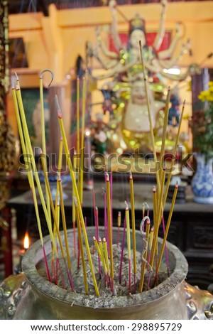 Smoking incence sticks at budhist pagoda - stock photo