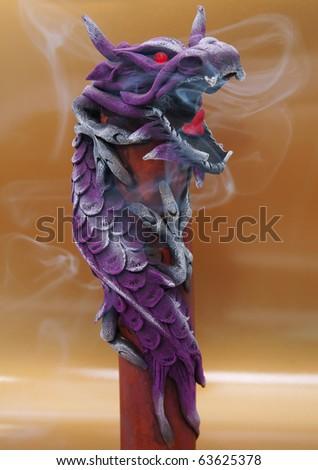 Smoking incense stick inside wooden dragon. - stock photo