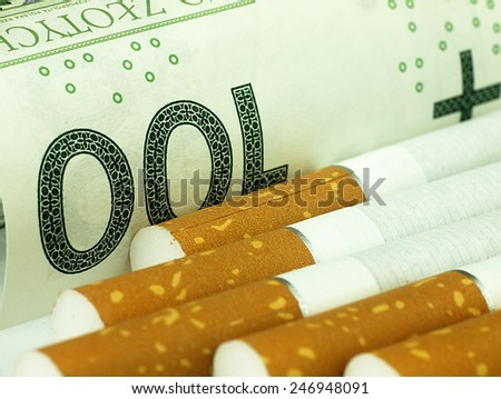 Smoking is expensive habit. Cigarettes on money background. - stock photo
