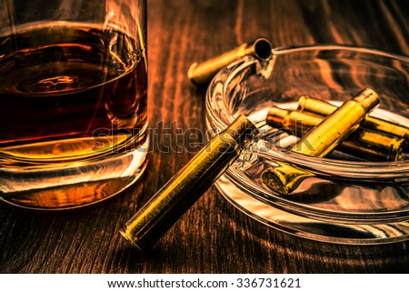 Smoking kills, empty casings from the rifle as a cigarette in an ashtray and glass of whiskey on a wooden table. Focus on the shell, image vignetting and the orange-blue toning - stock photo