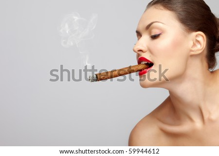 Smoking kills! Side portrait of attractive young woman smoking cigar, studio background. - stock photo