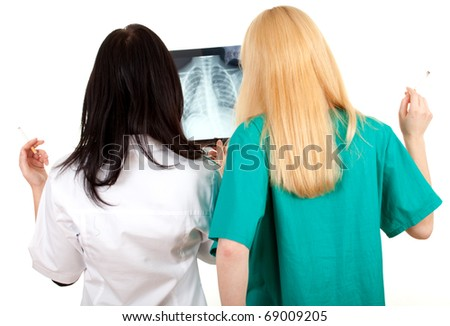 smoking lady doctors in uniforms looking at x-ray, chest, lungs - stock photo