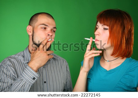 Smoking man and woman on green background - stock photo