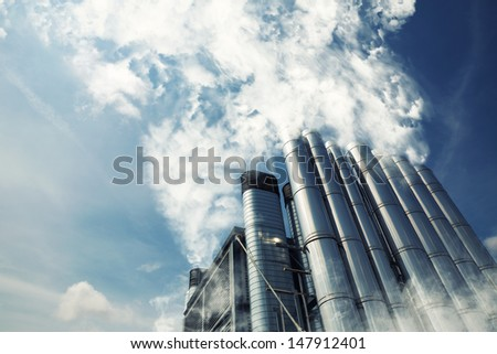 Smoking metal chimneys against blue sky - stock photo