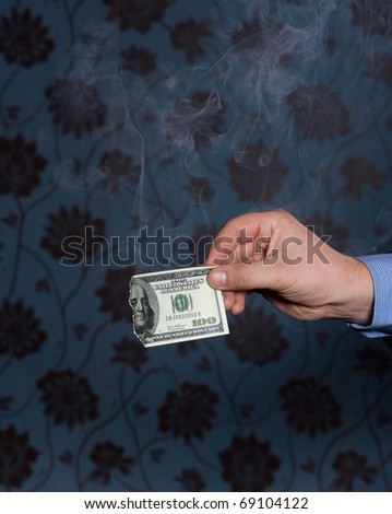 Smoking one hundred dollars bill in men's hand on dark background - stock photo