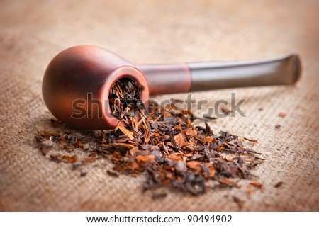 Smoking pipe and tobacco on linen canvas background - stock photo