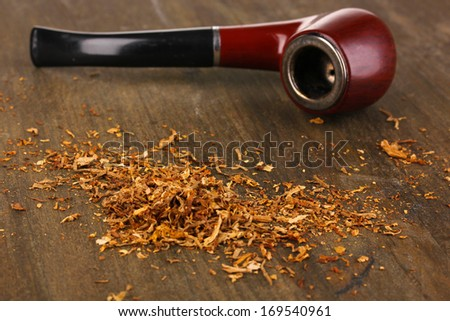 Smoking pipe and tobacco on wooden table close-up - stock photo
