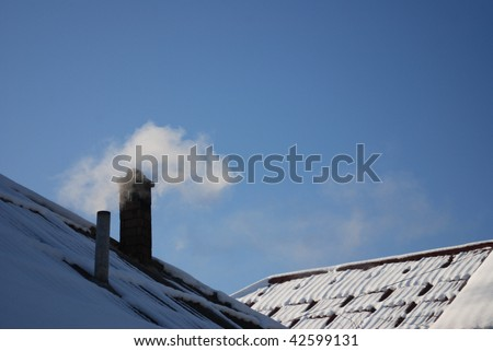 Smoking pipe on a snowy roof in a cold winter day