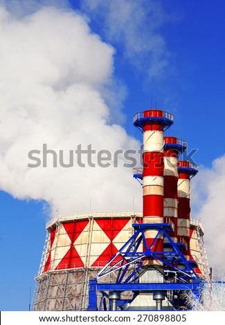 Smoking pipes of gas-turbine plant against blue sky - stock photo
