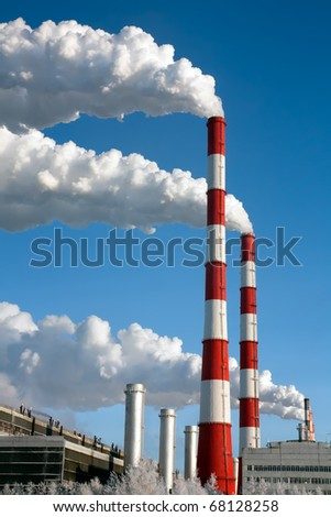 Smoking pipes of hydroelectric power station against the clear winter sky, Russia, Siberia