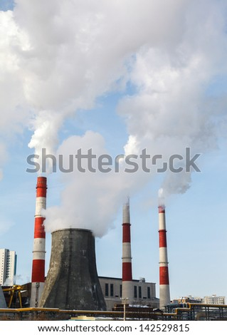 Smoking pipes of thermal power plant against blue sky