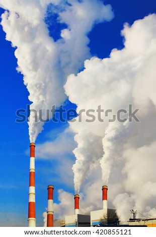 Smoking pipes of thermal power plant against blue sky - stock photo