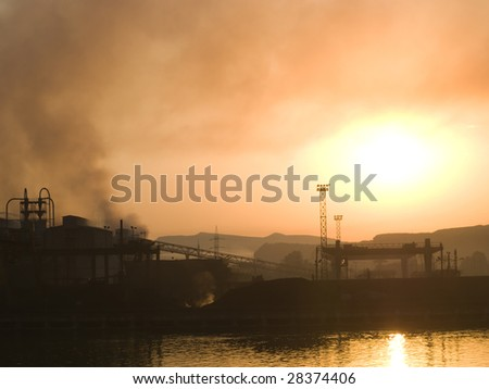Smoking plant near a river at sunset - stock photo