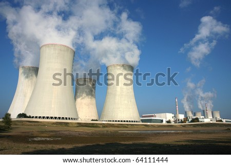 smoking power plant in agriculture field under blue sky - stock photo