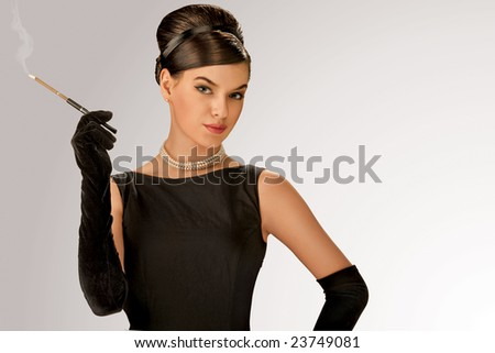 Smoking retro girl. A studio view of a woman in a retro style smoking a cigarette with a holder. - stock photo
