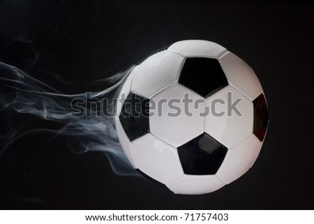 Smoking soccer ball illusion shot against a black background. - stock photo