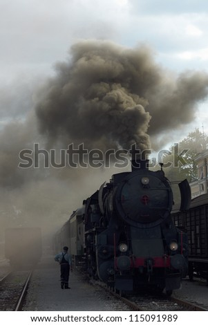 Smoking steam train on the track