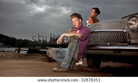 Smoking taxi driver and his girl near the vintage car. Retro-styled photo. - stock photo