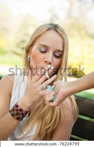 Smoking teenager - lighting cigarette - stock photo