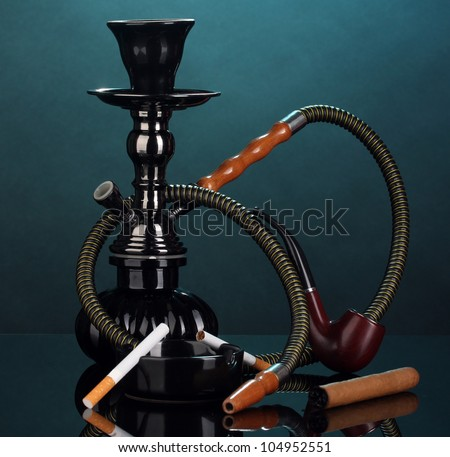 Smoking tools - a hookah, cigar, cigarette and pipe on blue background - stock photo