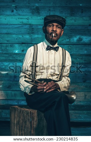 Smoking vintage african american senior jazz musician with trumpet in front of old wooden wall. Wearing suit and cap.