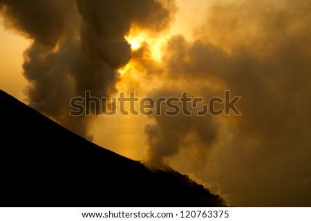 smoking volcano at sunset - stock photo