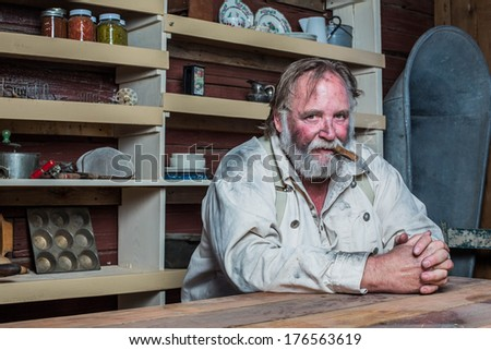 Smoking Western Man Looks Towards You as he Sits at Table - stock photo