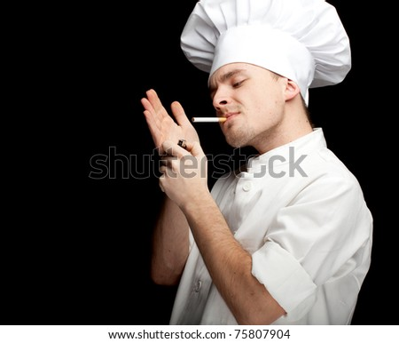 smoking young male cook in white uniform and hat, black bckground - stock photo