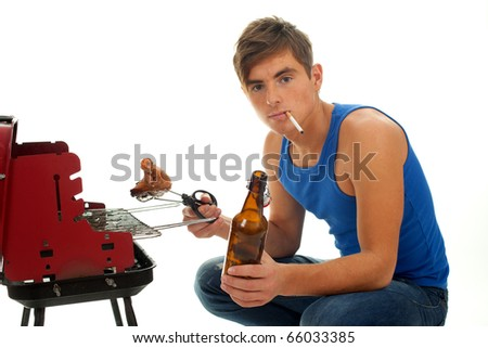 smoking young man in casual blue shirt grilling chicken and drinking beer