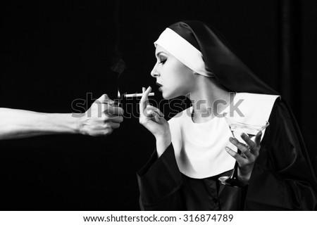 Smoking young nun. Studio shoot on black backround - stock photo