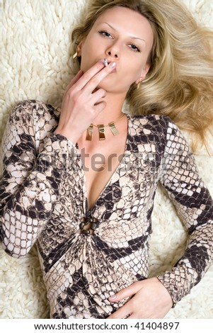 Smoking young pretty blonde on the carpet - stock photo