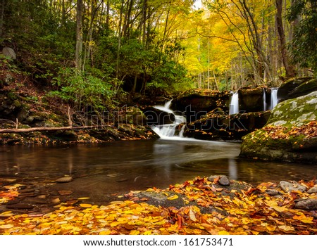 Smoky mountains waterfalls, three separate waterfall in the same shot, autumn leaves in the foreground and distant fall colors in the trees with a carpet of autumn leaves in the foreground  - stock photo