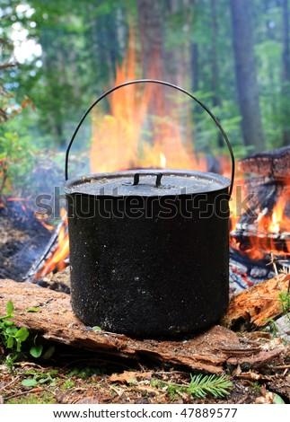 Smoky tourist kettle on fire background - stock photo