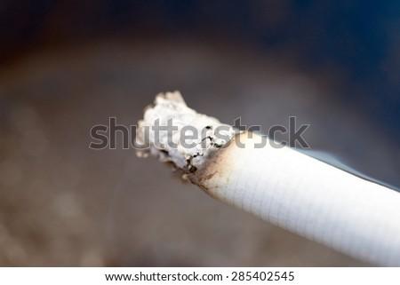 smoldering cigarette in an ashtray / smoldering cigarette - stock photo