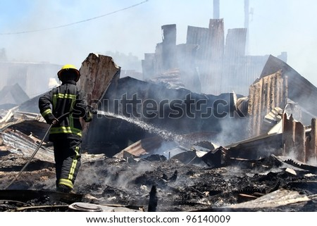 Smoldering remains of a ghetto house with a fireman spraying water - stock photo
