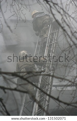 Smoldering remains of a ghetto house with a fireman spraying water firefighters extinguish a fire in an apartment house - stock photo