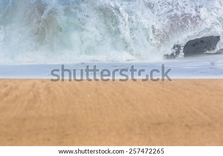 Smooth and sandy beach leading into the distance with detailed focus on the breakers of stormy sea - stock photo