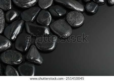 smooth black stones on black surface - stock photo