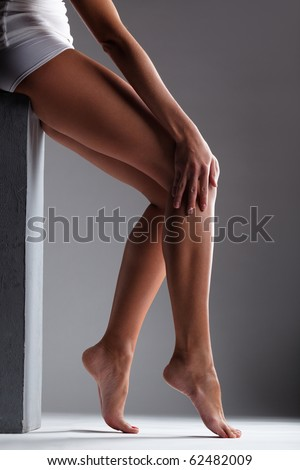 Smooth female legs on a grey background - stock photo