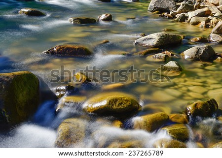 smooth flowing water at rocky river - stock photo