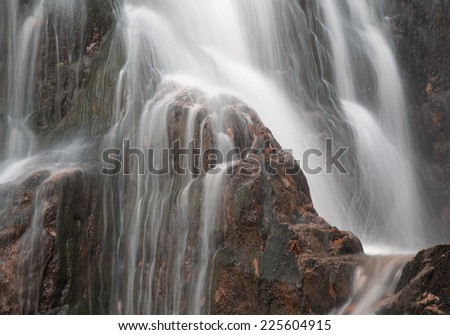 Smooth flowing waterfall over jagged rocks. - stock photo