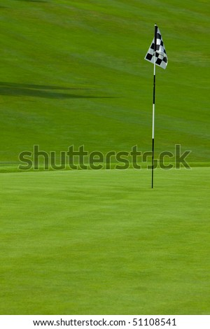 Smooth golf putting green with flag identifying location of the hole and a hill in the background