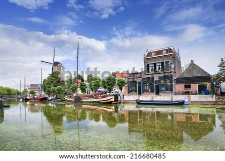 Smooth green canal with moored boats and monumental houses in the old town of Gouda, The Netherlands. - stock photo